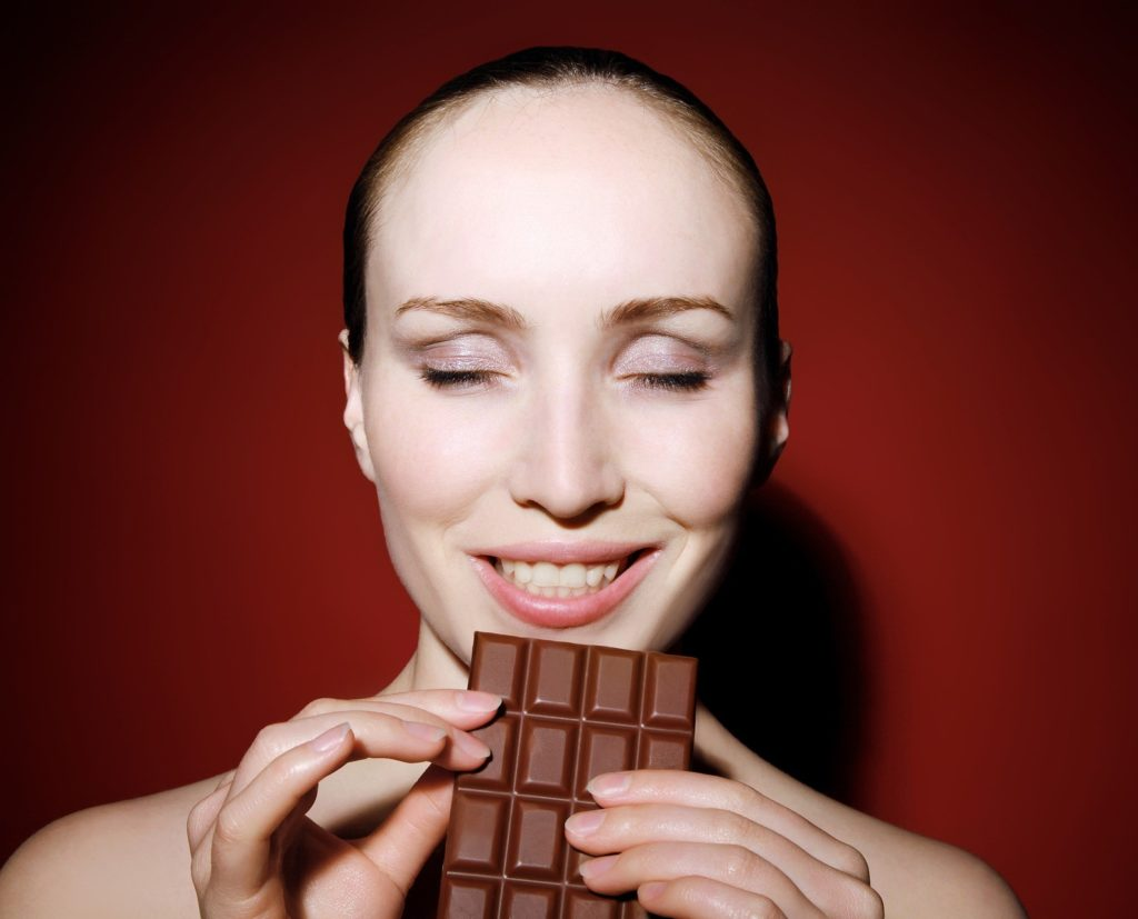 A woman eating chocolate. Click to learn about our 8 week custom keto meal plan.